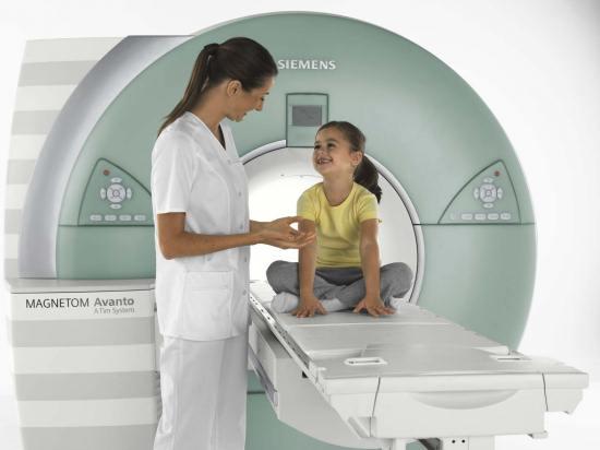 Лаборант успокаивает ребенка перед магнитно-резонансной томографией