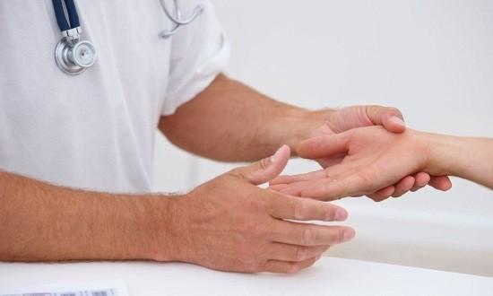Доктор проводит осмотр кисти и лучезапястного сустава