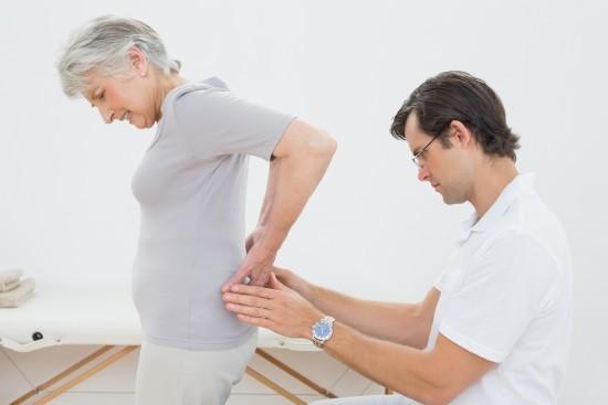 Женщина жалуется на боли в поясничном отделе позвоночника