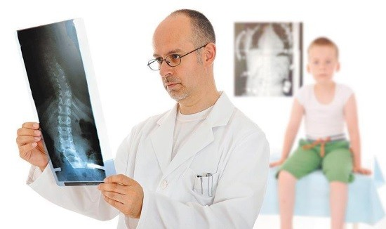 Доктор анализирует снимок позвоночника