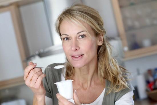 Женщина ест йогурт