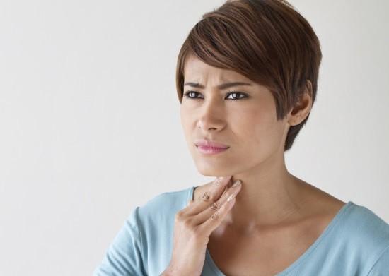 Женщина страдает от боли в горле