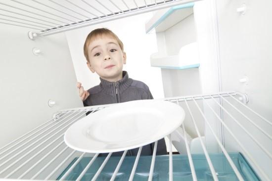 Мальчик заглядывает в пустой холодильник